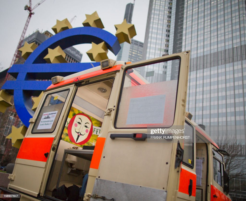 A disused ambulance is parked in front of the euro sculpture at the headquarters of the European Central Bank in Frankfurt am Main, central Germany, on January 3, 2013. Members of the 'occupy' movement parked the car as a symbolic opportunity to treat bankers.AFP PHOTO / FRANK RUMPENHORST GERMANY OUT