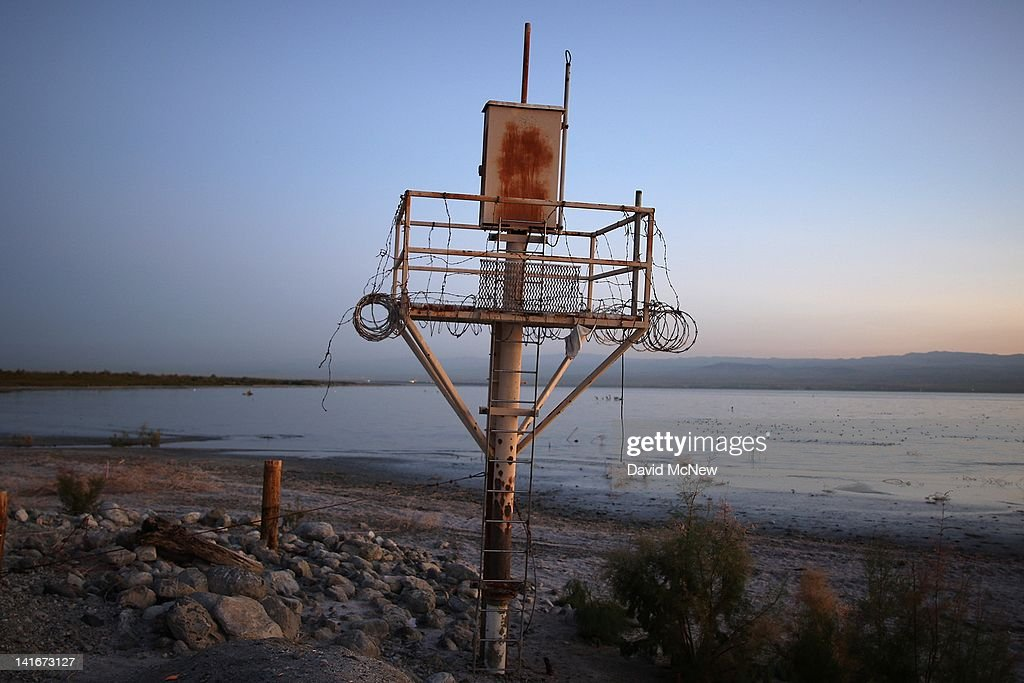 A disused structure on the shore of the Salton Sea is seen an area where a controversial development would create a new town for nearly 40,000 people on the northwest shore of the biggest lake in California, the Salton Sea, on March 21, 2012 south of Mecca, California. The Center for Biological Diversity and the Sierra Club have filed a lawsuit against Riverside County after the Board of Supervisors approved a record-sized development project for Riverside County, saying that it would increase pollution and threaten wildlife in nearby parks at the Salton Sea and in the largest state park in California, Anza-Borrego Desert State Park. Though massive fish die-offs occur annually, drawings in the Travertine Point plans feature peaceful marinas but the lake has been plagued by dropping water levels and increasing salt levels for decades. Scientists say that a catastrophic decline in the fish population is inevitable and a resulting 25 to 50 percent drop in the migratory bird population will destroy a major stopping point in the Pacific bird migration route. The shrinking salt lake is exposing more and more fine dust, posing health problem as blows it across the region. Funding to stop the ecological collapse of the sea is not likely in the near futures with its $9 billion price tag.