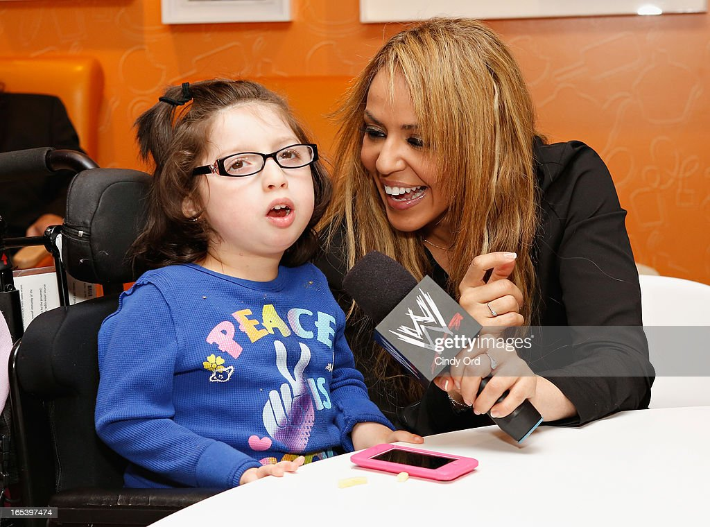 WWE Diva Layla El sings with a child during a visit to St. Mary's Hospital For Children on April 3, 2013 in New York City.