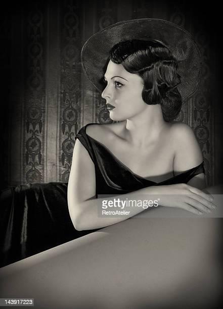 Diva mit Hut in film-noir-Stil.