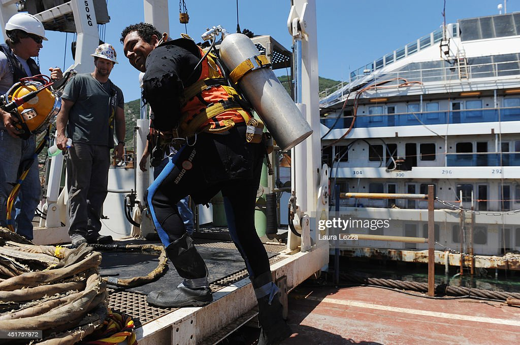 A diver and Titan-Micoperi workers are seen while the last sponson is installed on the port side of the wrecked ship Costa Concordia on July 3, 2014 in Isola del Giglio, Italy. A total of 30 sponsons have been attached to the Costa Concordia to re-floate the ship wreck around July 10th. The wreckage will be removed by the end of July 2014 and will be toed to the port of Genoa for dismantling.