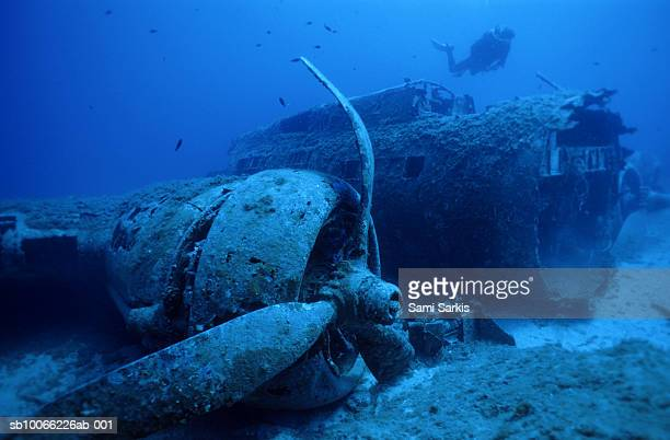 Diver exploring sunken B17 airplane wreck on seabed