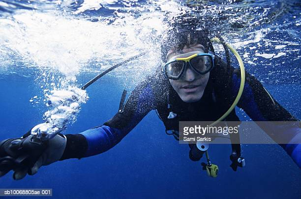 Diver holding regulator out of mouth under water surface, portrait