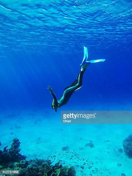 Mergulhador no azul profundo do mar