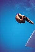 Diver in pike position off of platform