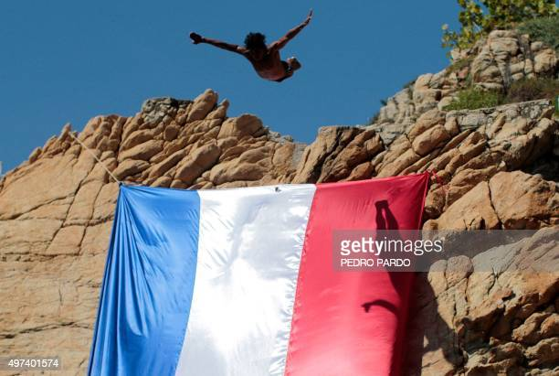 A diver jumps from La Quebrada cliff in Acapulco Mexico on November 16 which was adorned with the French flag in solidarity with the victims of Paris...