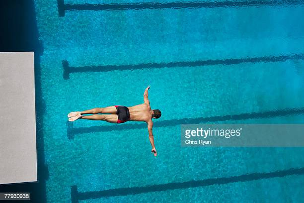 Diver midair going into pool