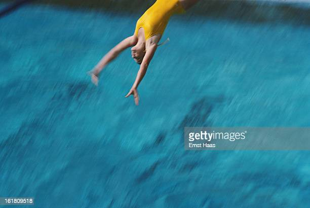 A diver plunges into a swimming pool March 1984