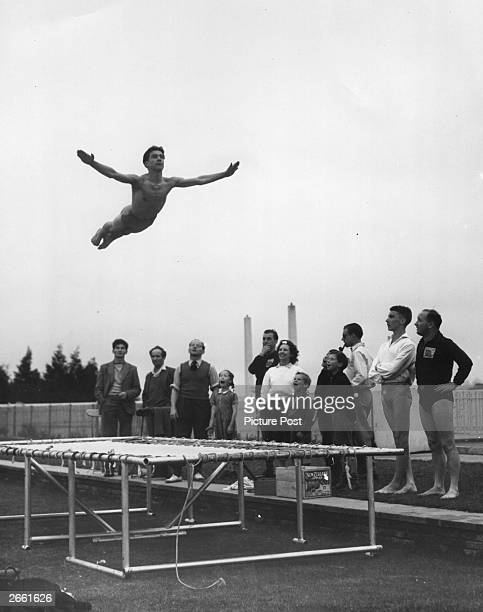 A diver practising on a trampoline at Finchley swimming baths London watched by admiring spectators Original Publication Picture Post 5750 Diving At...