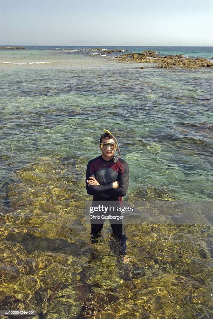 Diver standing in shallow water at ocean