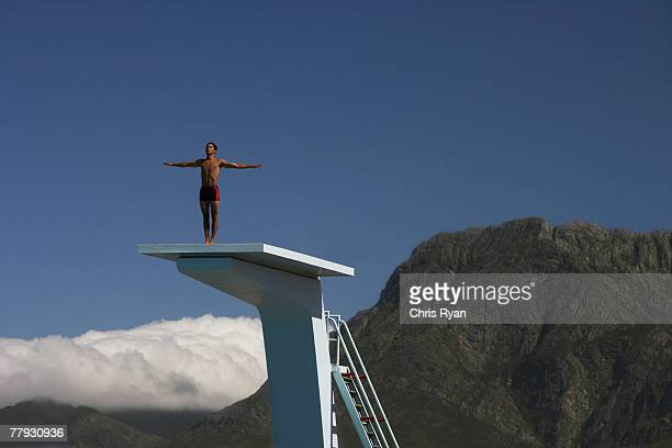 Diver standing on a diving board in a scenic location