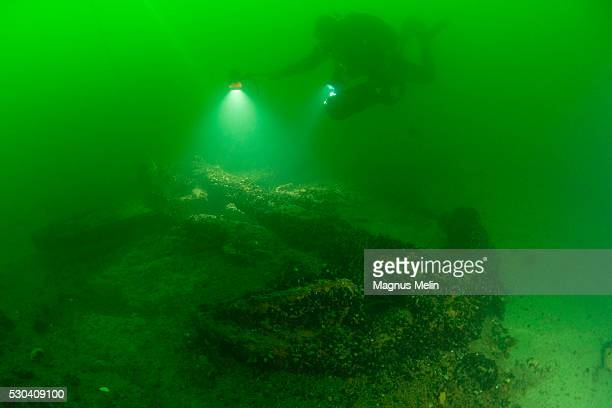 Diver swimming next to ship wreck