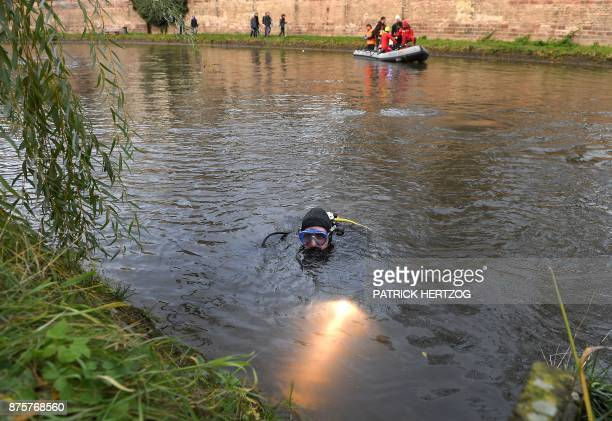 A diver uses a light during a cleanup mission through the Ill river in Strasbourg eastern France on November 18 2017 Hundreds of citizens and some...