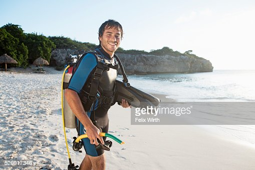 Diver wearing wetsuit standing on beach : Stockfoto