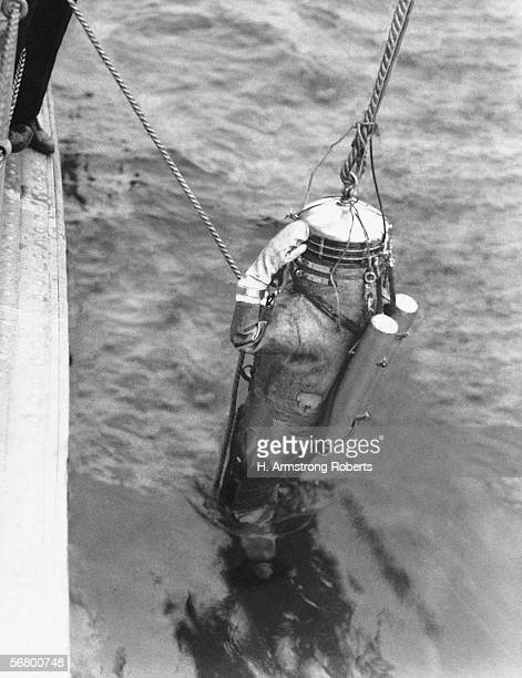 Diver with two oxygen cylinders on strapped on back being lowered into water