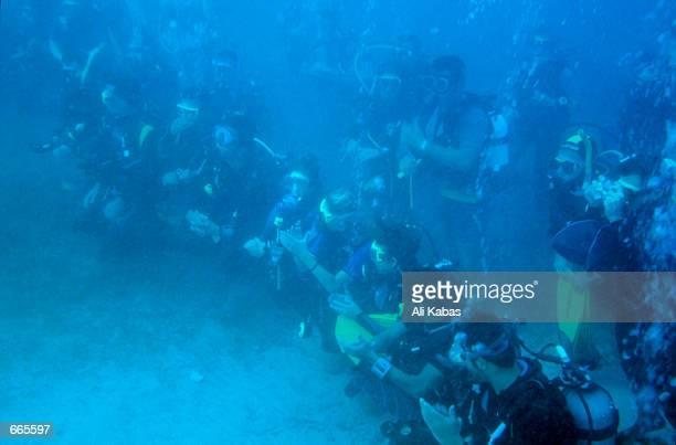 Divers applaud as the Turkish sculptor Kemal Tufan unveils the world's first underwater sculpture September 23 2000 near the southern town of Kas...