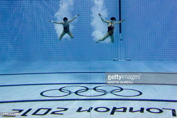 Divers are pictured in the pool after performing their jump during a training session on July 25 2012 at the Aquatics center in London two days...