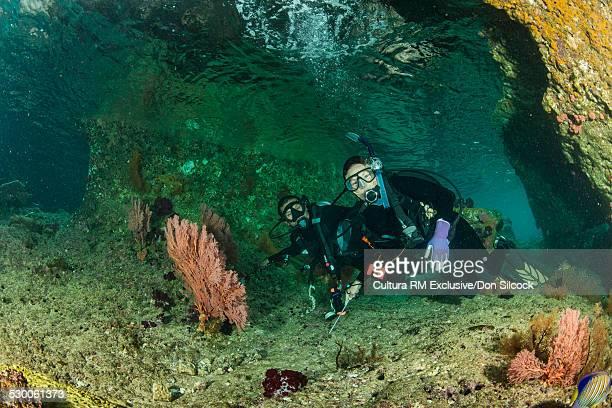 Divers explore the swimthrough at Batu Lima (Five Rocks) in the Dampier Strait, Raja Ampat, West Papua, Indonesia