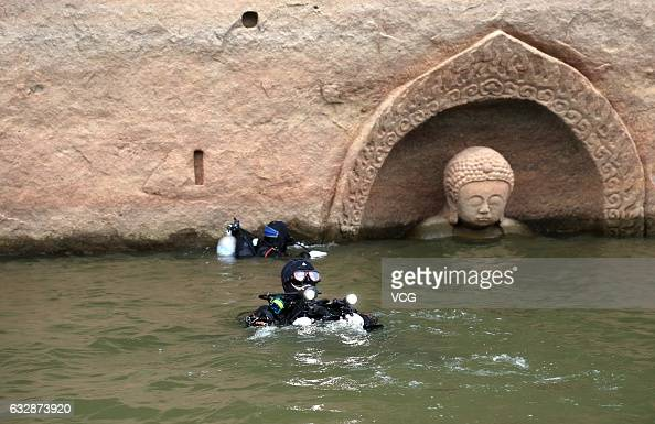 Divers investigate a buddha statue found on the shore of a dam on January 9 2017 in Fuzhou Jiangxi Province of China According to archaeologists'...