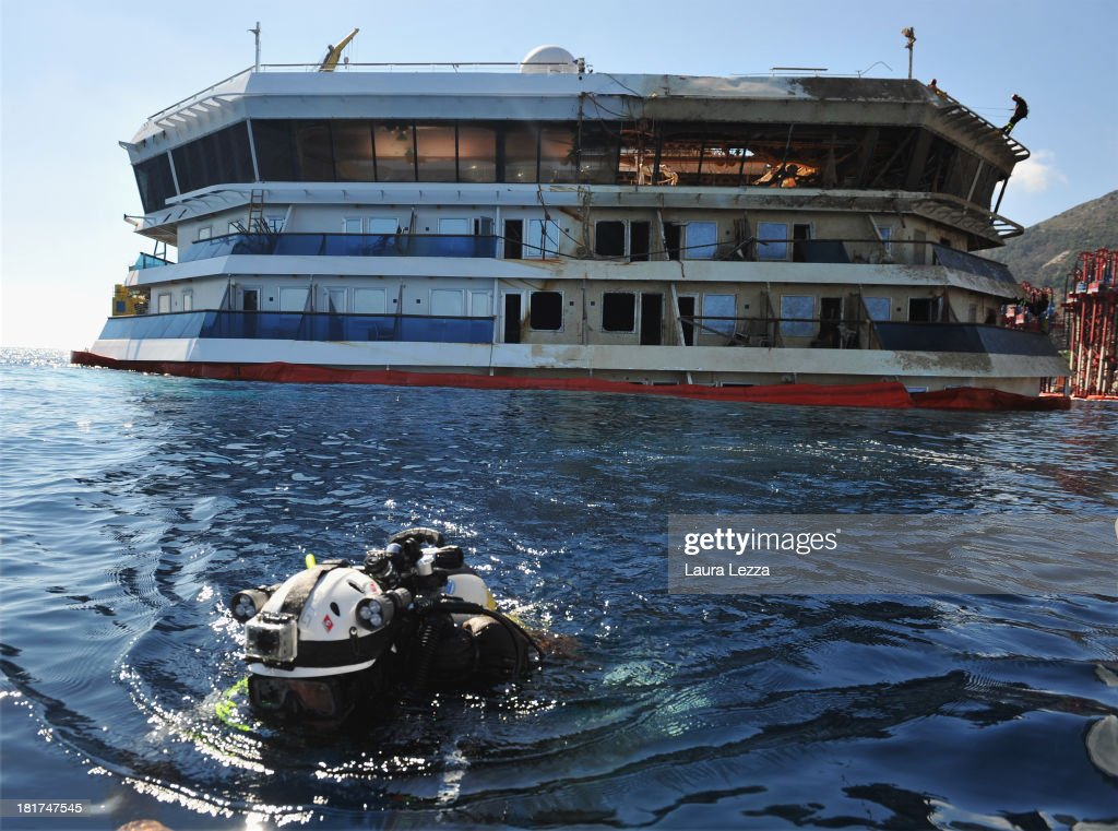 Divers of the Nucleo Operatori Subacquei Guardia Costiera (Coast Guard) and firefighters conduct a search operation onboard the Costa Concordia on September 24, 2013 in Giglio Porto, Italy. Today the search resumed for the missing bodies of Maria Grazia Tricarichi and Russsel Rebello, whose bodies were never found after the Costa Concordia capsized on January 13, 2012, leaving 32 people dead. Specialist divers from the coastguard, fire brigade and police have begun searching the area between the righted ship and the coast and other parts of the vessel which were previously off limits.