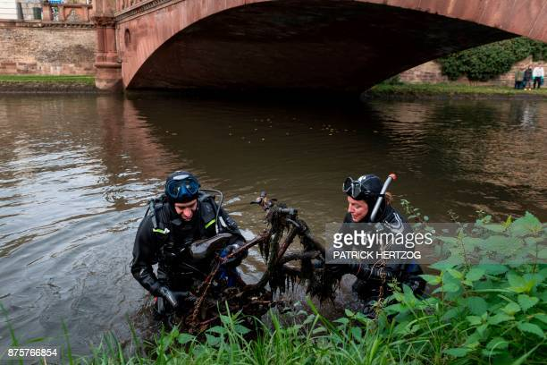 Divers pull a bike out of the Ill river during a cleanup mission in Strasbourg eastern France on November 18 2017 Hundreds of citizens and some...