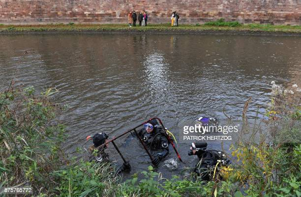 Divers pull a roadwork fence out of the Ill river during a cleanup mission in Strasbourg eastern France on November 18 2017 Hundreds of citizens and...