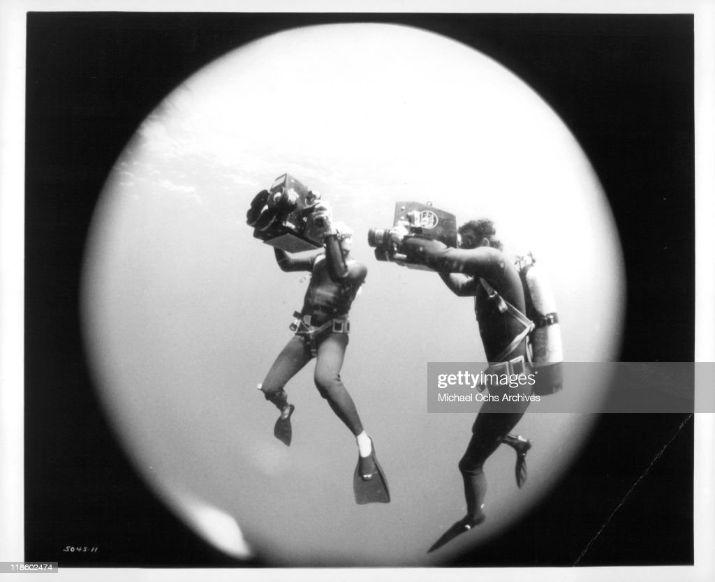 Divers underwater with cameras in a scene from the film 'Blue Water, White Death', 1971.