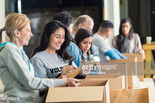 Diverse adults packing donation boxes in charity food bank