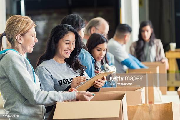Vielfältige Erwachsene Packen Spendenboxen in charity food bank