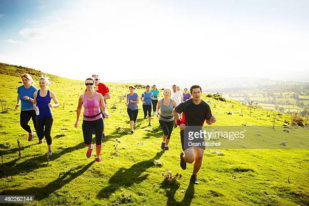 Diversas adultos correr al aire libre en las montañas
