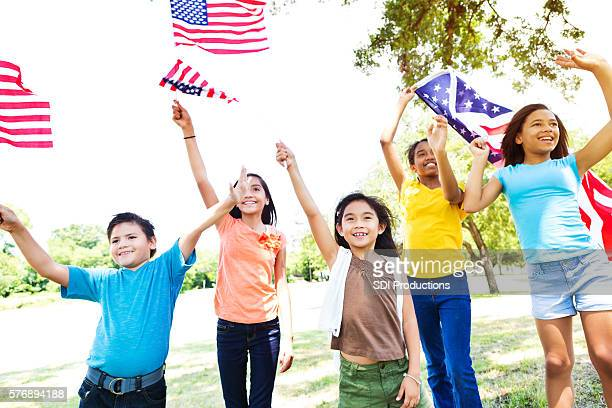 Diverse American kids wave American flags