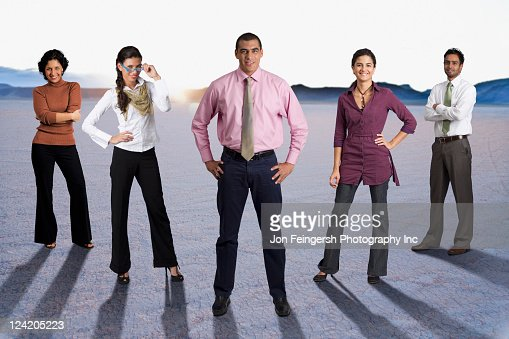diverse business people standing together in desert stock