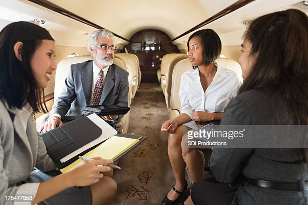 Diverse business team working on board company jet