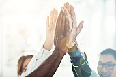 Diverse group of businesspeople high fiving each other while standing in a huddle together in a bright modern office