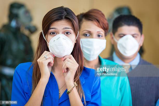 Diverse businesspeople wearing protective medical face masks during flu season