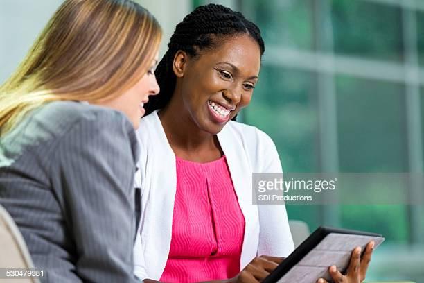 さまざまな businesswomen デジタルタブレットを使用して、オフィスのロビー