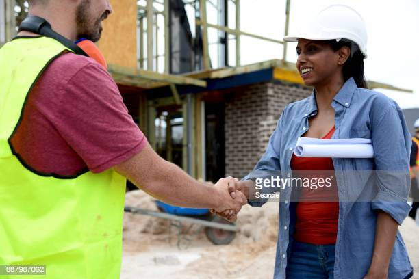 SYD112017 Diverse construction workers shaking hands