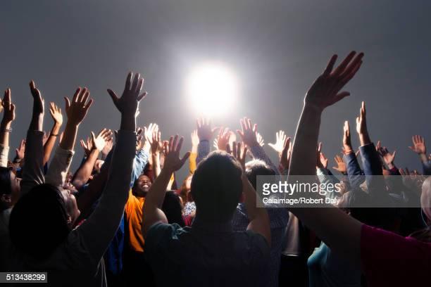 Diverse crowd cheering around bright light
