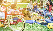 Diverse culture friends making picnic on city park outdoor - Young trendy people eating dinner in backyard outside - Focus on african hair girl - Youth and friendship concept - Vintage retro filter