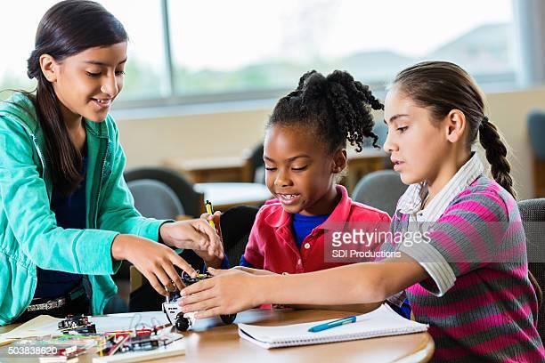 Diverses jeunes filles bâtiment de l'école primaire en classe de sciences robot