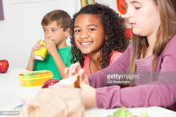 Diverse elementary students eat lunch in classroom