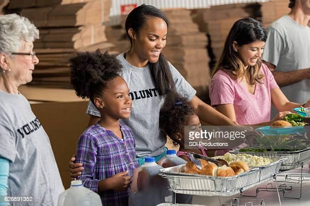 Diverse family volunteers together in soup kitchen