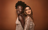 Portrait of two women standing back to back in studio. Diverse females standing on brown background.