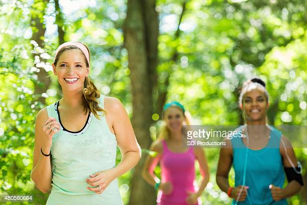 Diverse female runners jogging together in park