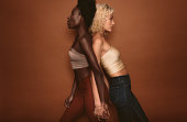 Two women standing with backs against each other. Side view studio shot of diverse females standing on brown background.