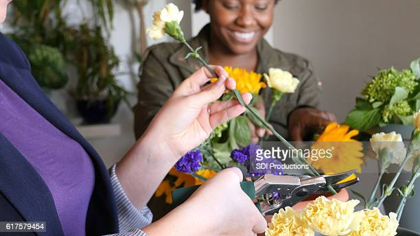 Diverse florists prepare floral arrangements