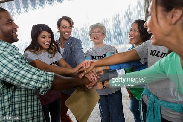 Diverse friends cheer before beginning volunteering at food bank