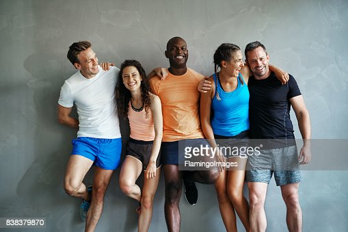 Diverse friends in sportswear laughing together in a gym : Stock Photo