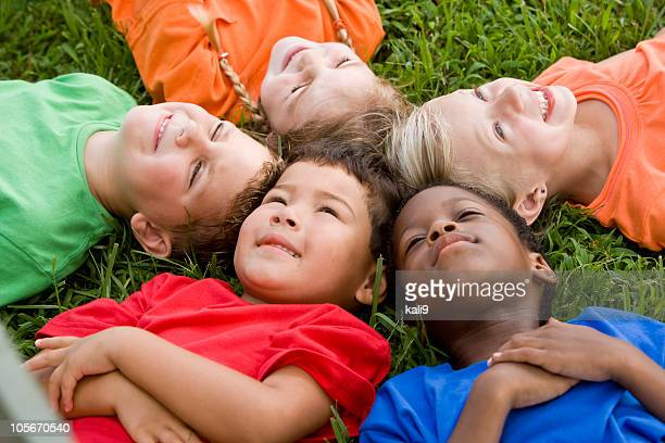 Diverse group of children, heads together showing unity, friendship