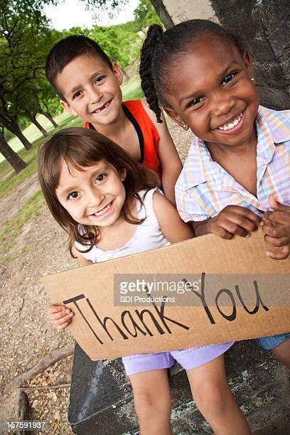 Grupo de diversas crianças segurando sinal de agradecimento
